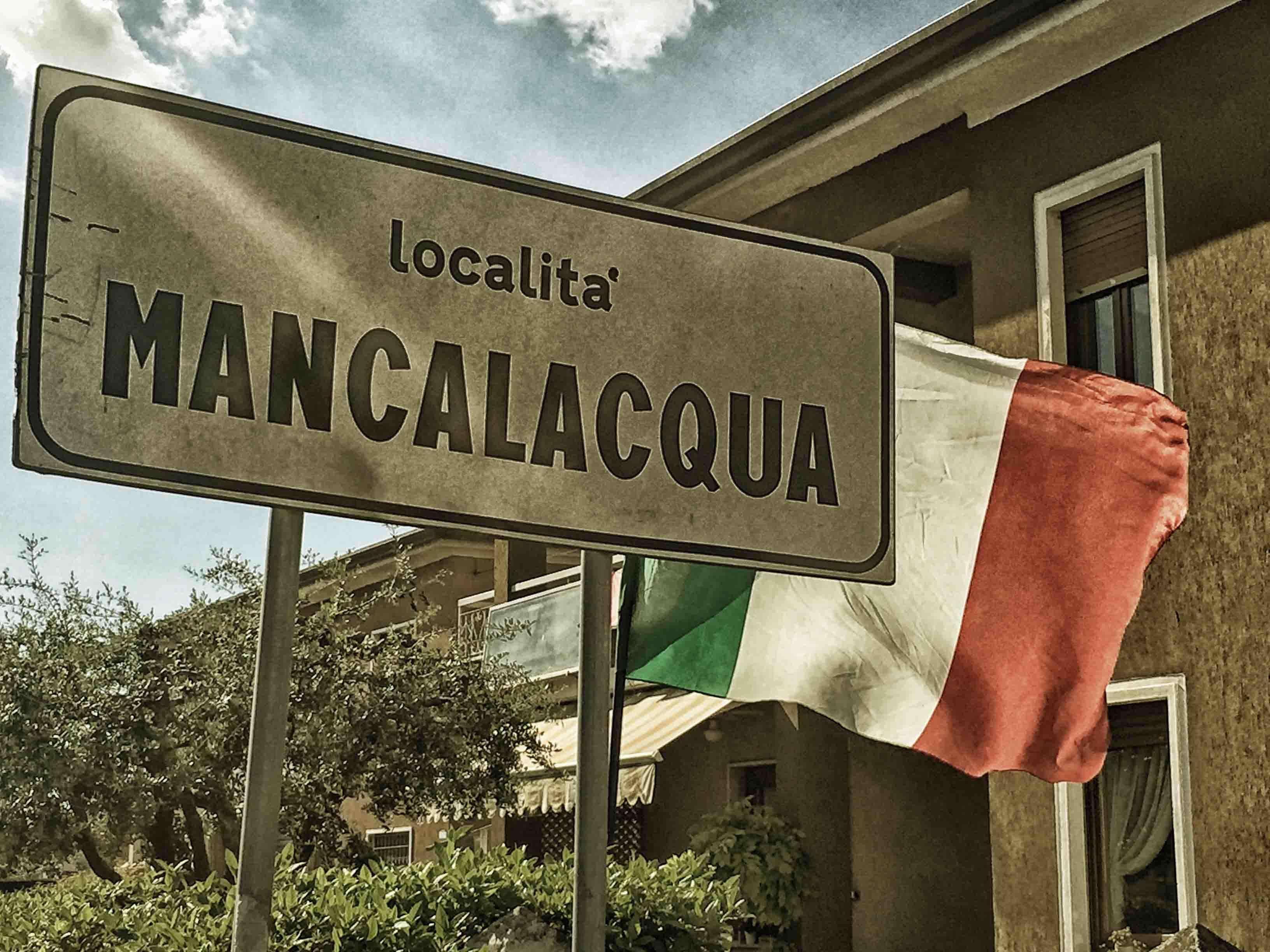 Il cartello di Mancalcqua. Sopra, l'ingresso di Mancalacqua provenendo da Sona negli anni ottanta